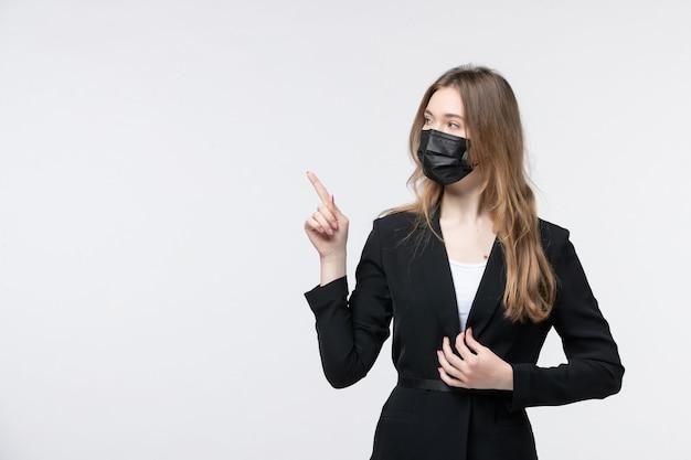 Vista frontale della giovane donna bionda in tuta che indossa maschera chirurgica e punta verso l'alto su bianco