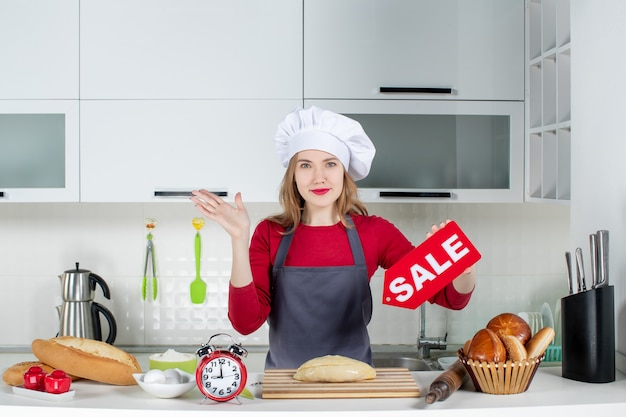 Vista frontale giovane donna bionda in cappello da cuoco e grembiule con cartello di vendita in cucina