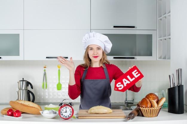 料理の帽子とエプロンの正面図金髪の若い女性がキッチンで販売サインを保持しています