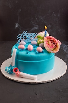 A front view blue birthday cake with flower on top cake color