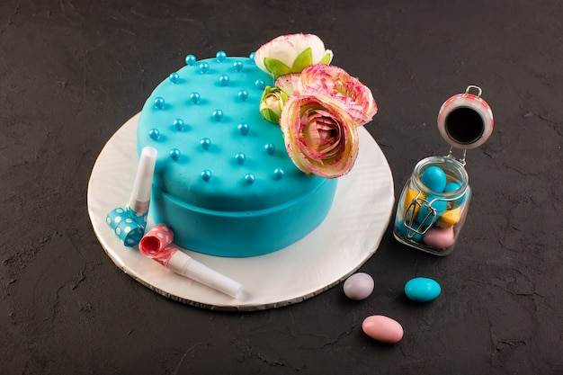 A front view blue birthday cake with flower on top and decors