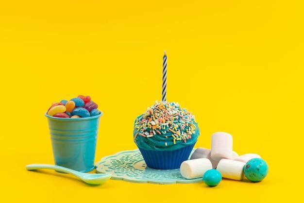Una torta blu vista frontale con candela insieme a marmellate colorate e marshmallow su colore giallo, zucchero dolce biscotto
