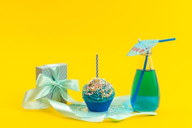 Una torta blu di vista frontale con il piccolo contenitore di regalo della candela e bevanda sul colore giallo e dolce della bevanda