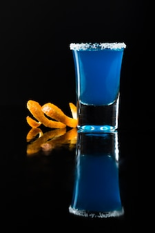 Front view of blue cocktail in shot glass with orange peel and salt rim