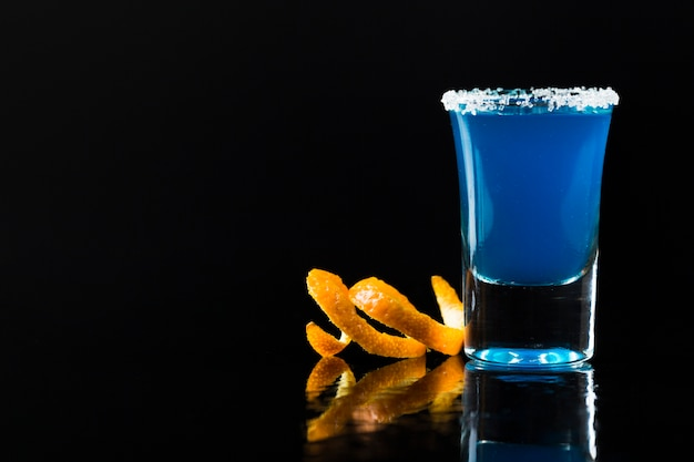Front view of blue cocktail in shot glass with orange peel
