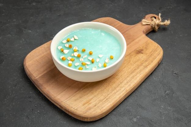 Вид спереди синий ледяной десерт внутри тарелки на темном полу кремового цвета