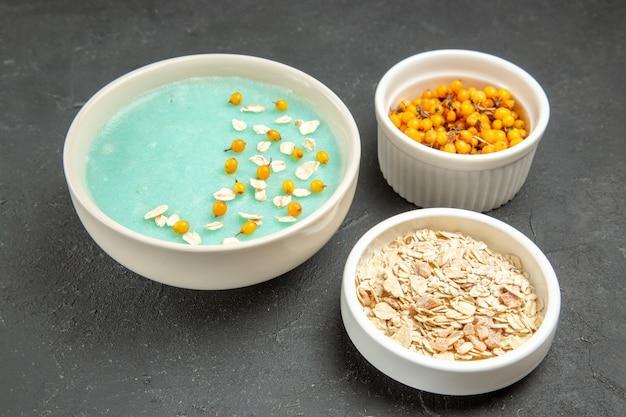 Dessert ghiacciato blu di vista frontale con muesli crudo sulla colazione scura del gelato della crema della tavola