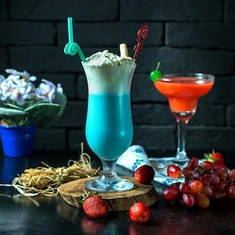 Вид спереди синий молочный коктейль с клубникой и виноградом