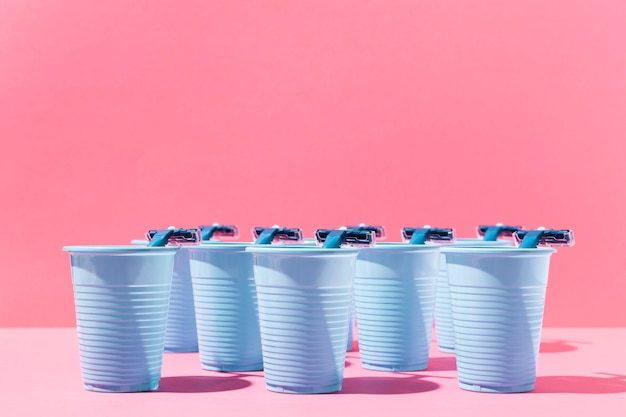 Вид спереди синие пластиковые стаканчики и бритвенные лезвия
