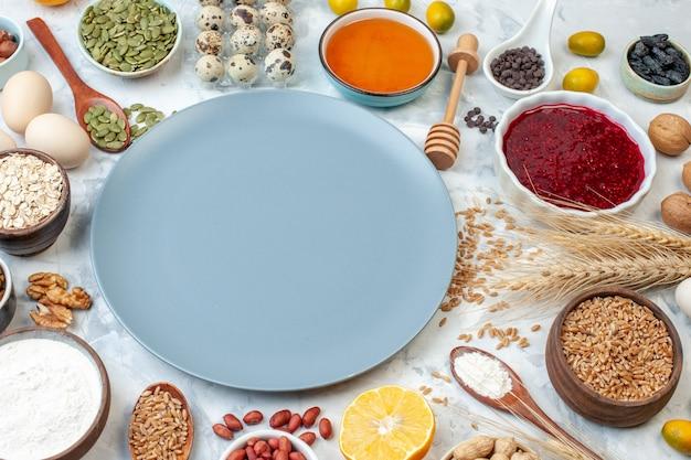 正面図小麦粉ゼリー卵と白い背景の上のさまざまなナッツと青いプレート生地フルーツケーキ砂糖写真色パイナッツ甘い