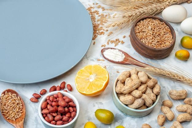 正面図小麦粉ゼリー卵と白い背景の上のさまざまなナッツと青いプレート砂糖色生地フルーツ写真パイナッツ甘いケーキ