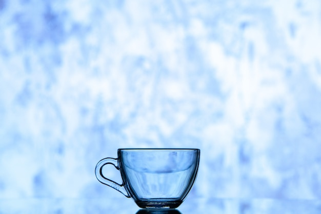 Front view blue water glass on blue white blurry background copy space