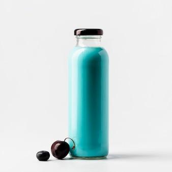 Vista frontale della bottiglia di succo di mirtillo e ciliegia con frutta