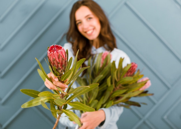 Front view blurred woman posing with flowers
