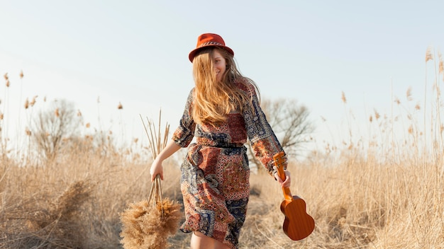 Front view of bohemian woman in nature holding ukulele