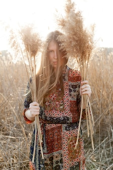 Front view of bohemian woman posing in nature field