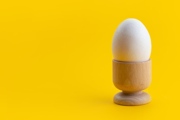 A front view boiled egg white, whole and inside little stand on yellow, food meal color