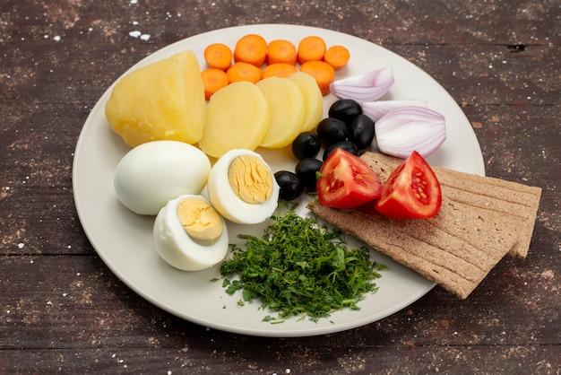 茶色の背景の野菜食品の食事の朝食にプレートの内側のオリーブグリーンガーリックとトマトとゆで卵の正面図