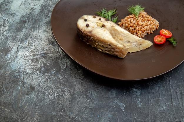 Vista frontale di pesce bollito e farina di grano saraceno servita con pomodori verdi su un piatto nero sulla superficie del ghiaccio con spazio libero