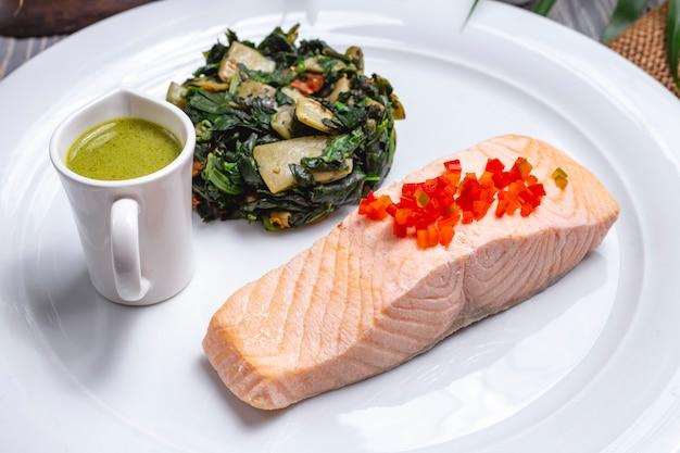 Vista frontale bollito pesce rosso con verdure stufate e salsa su un piatto