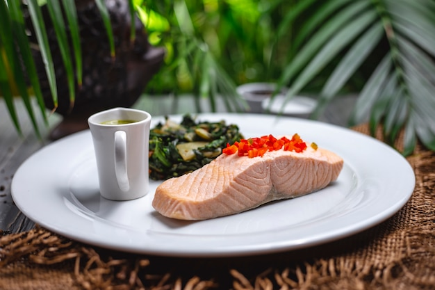 Front view boiled red fish with stew greens and sauce on a plate