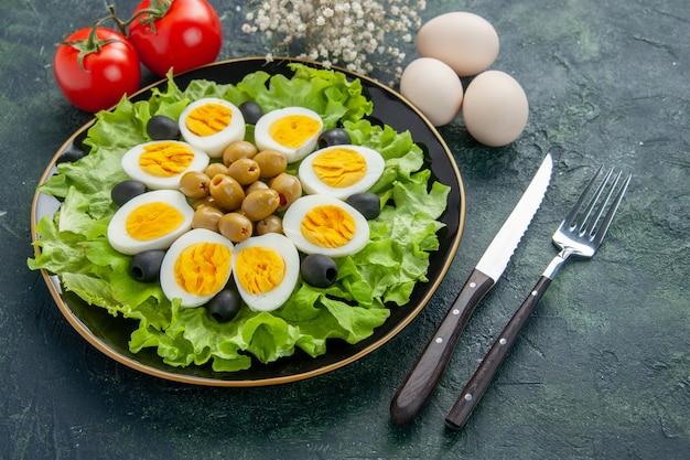 Вид спереди вареные нарезанные яйца с зеленым салатом и оливками на темном фоне