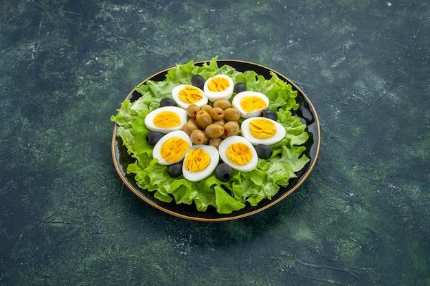 Вид спереди вареные нарезанные яйца с оливками и зеленым салатом на темно-синем фоне