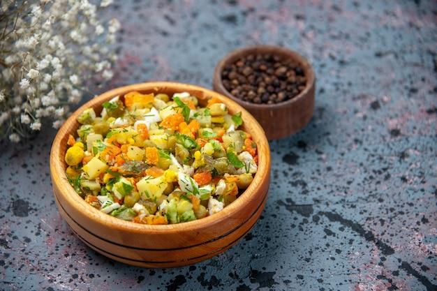 正面図青の背景にコショウと茹で野菜サラダ