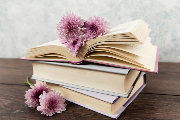 Front view of books and flowers on wooden table