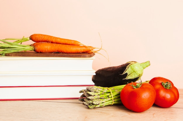 Front view of books and vegetables with plain background