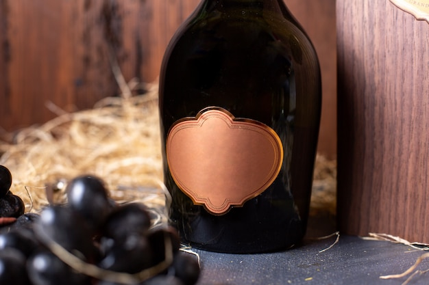 A front view bottle of alcohol black bottle with golden cap along with black grapes and green leaves on the brown background drink winery alcohol