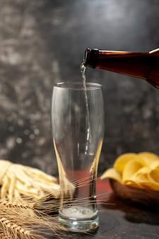 Vista frontale bottiglia di orso che versa nel bicchiere su sfondo chiaro