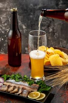 Vista frontale bottiglia di orso che si versa nel bicchiere con cips e pesce su uno sfondo chiaro