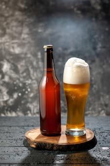 Vista frontale bottiglia di orso con bicchiere pieno di orso su sfondo chiaro