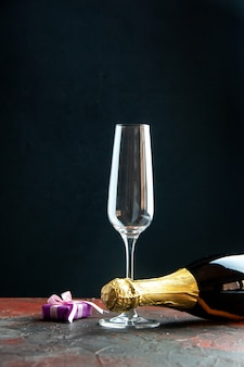 Front view bottle of champagne with wine glass on dark background