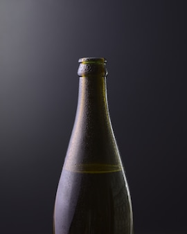 Front view of a bottle of cold beer with dark black background with purple gradient colors. cold alcoholic beverage, international beer day concept.