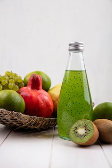 Front view bottle of green juice with pomegranates grapes tangerines and pear in a basket on a white wall