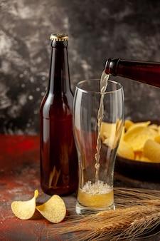 Вид спереди бутылка медведя вливается в стакан с чипсами на темном фоне