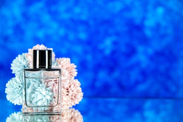 空きスペースと青い背景の上の香水の花の正面図のボトル