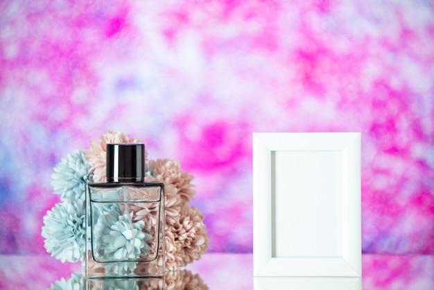 Флакон духов, вид спереди, маленькая белая рамка для фотографий на розовом размытом фоне