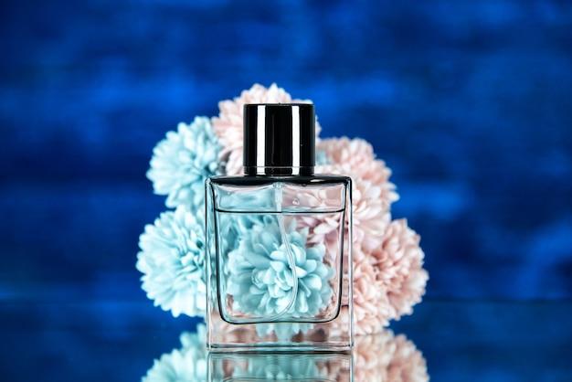 Vista frontale della bottiglia di fiori di profumo su sfondo sfocato blu
