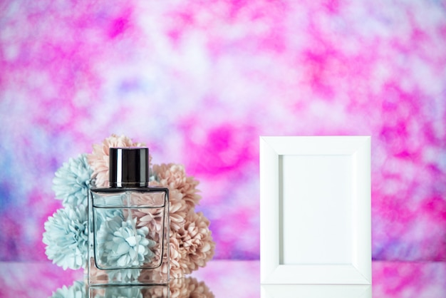 Front view bottle of perfume small white picture frame flowers on pink blurred background
