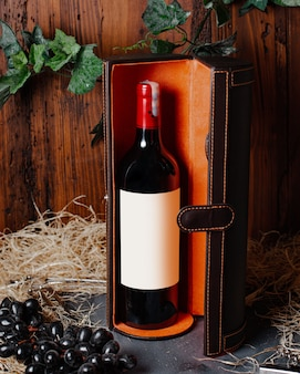 A front view bottle of wine red wine with burgundy cap inside box alcohol winery