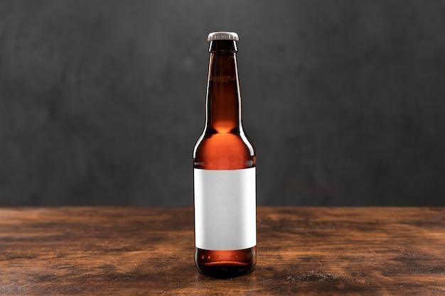 Bottiglia di vista frontale con birra e adesivo in bianco sul tavolo