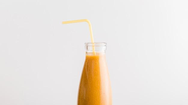 Bottiglia vista frontale con frullato d'arancia e paglia