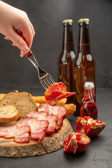 Front view bottles of bear with ham slices and bread on a dark background