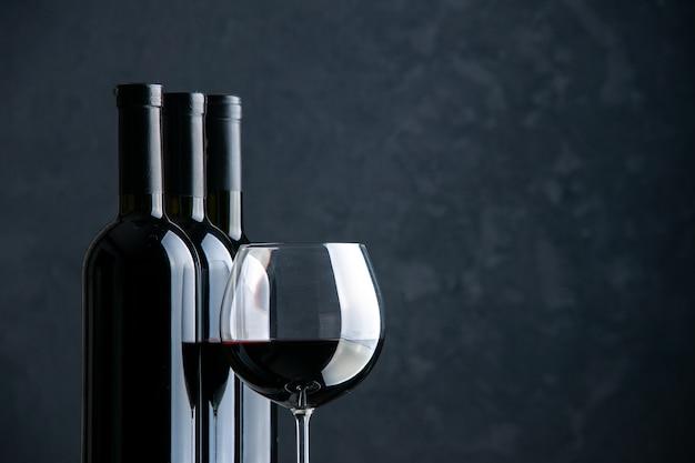 Вид спереди бутылки вина с бокалом вина на темной поверхности