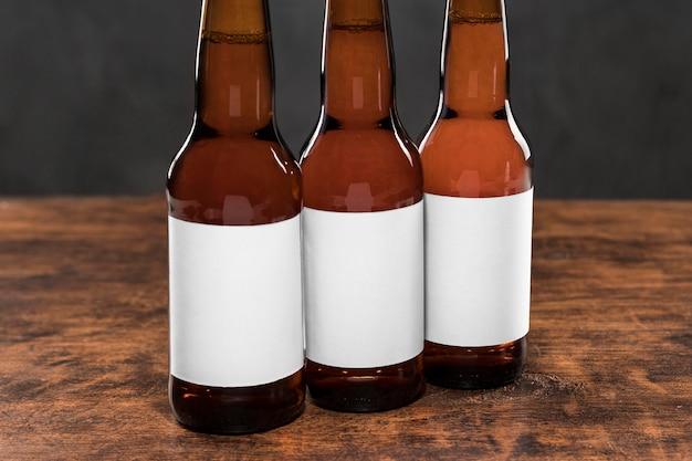 Bottiglie di vista frontale con birra ed etichette vuote