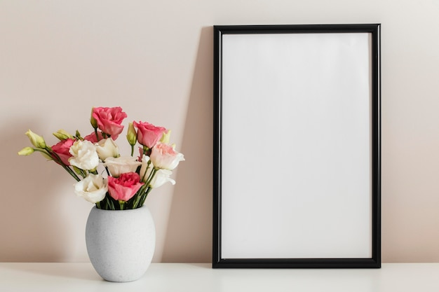 Front view bouquet of roses in a vase with empty frame