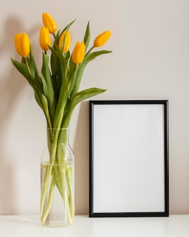 Front view bouquet of tulips in a vase with empty frame